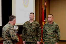 Lt. Gen. Terry G. Robling, commander, U.S. Marine Corps Forces, Pacific, presents the trophy for the Marine Corps Band of the Year Award to Chief Warrant Officer 3 Michael J. Smith, band officer, MarForPac Band, and Master Gunnery Sgt. Mark D. Gleason, bandmaster. The award is given to the best of the 10 field bands in the Marine Corps.