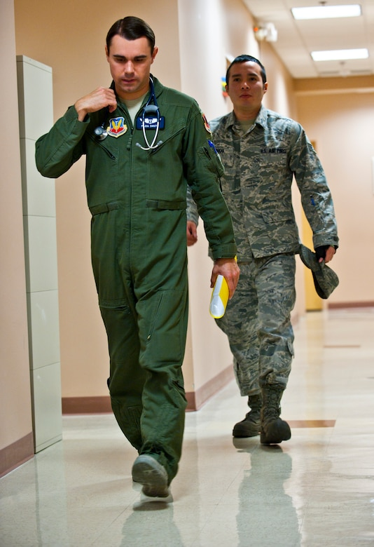 U.S. Air Force Capt. (Dr.) Thomas Shute, 42nd Attack Squadron flight surgeon, walks with his patient, Senior Airman Phou Johnson, 757th Aircraft Maintenance Squadron avionics technician, during an occupational health exam Jan. 10, 2014, at Nellis Air Force Base, Nev. Occupational health exams help flight surgeons have a better understanding of what aircrew members endure in the environments they work in. (U.S. Air Force photo/Senior Airman Brett Clashman)