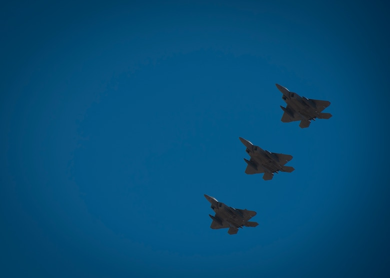 Three F-22 Raptors fly in formation over the base during their departure from Holloman Air Force Base, N.M., Jan. 6. The first five of 24 combat-deployable F-22 Raptors left Holloman heading to Tyndall Air Force Base, Fla. as a permanent change of station. The five F-22s that left Jan. 6 will be followed by six Raptors leaving each month until the move is completed. (U.S. Air Force photo by Airman 1st Class Aaron Montoya)