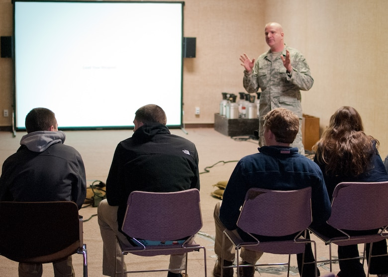 Master Sgt. Sean Dias, of the 102nd Security Forces Squadron talks with students from Sandwich Highschool on use-of-force techniques, laws, and concepts on Otis Air National Guard base, December 12, 2013. The students training was part of a law enforcement class and included the use of situation simulator which trains people how to react when faced with different law enforcement scenarios. (National Guard photo by Master Sgt. Aaron Smith/Released)