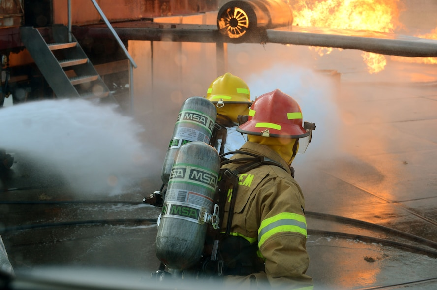 SPANGDAHLEM AIR BASE, Germany – U.S. Air Force firefighters suppress fires during a training exercise Jan. 8, 2014. During this training, fires reach upward of 500 degrees Fahrenheit inside a mobile aircraft fire trainer. (U.S. Air Force photo by Airman 1st Class Kyle Gese/Released)