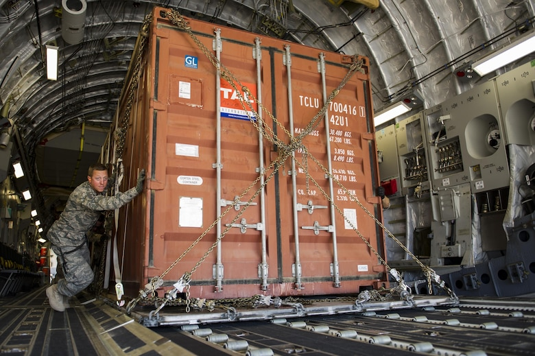 Tech. Sgt. James Schenck, 405th Logistics Readiness Squadron cargo and special handling noncommissioned officer in charge, pushes a container express box off a C-17A Globemaster III and onto a K-loader at an undisclosed location in Southwest Asia, Dec. 31, 2013. Schenck is deployed from Peterson Air Force Base, Colo., and is assigned to the 405th Air Expeditionary Group. (U.S. Air Force photo by Staff Sgt. Stephany Richards)