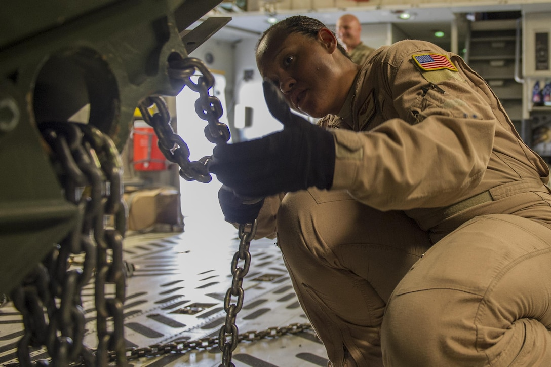 Staff Sgt. Orial Christopher, 817th Expeditionary Airlift Squadron loadmaster, secures cargo in a C-17A Globemaster III at Kandahar Airfield, Afghanistan, Jan. 3, 2014. Christopher is deployed from Joint Base Charleston, S.C., in support of the 405th Air Expeditionary Group. The 405th AEG supports U.S. Central Command's Deployment and Distribution Operation Center, a strategically located air, land and sea logistics hub, playing a critical role in the U.S. departure from Afghanistan. (U.S. Air Force photo by Staff Sgt. Stephany Richards)
