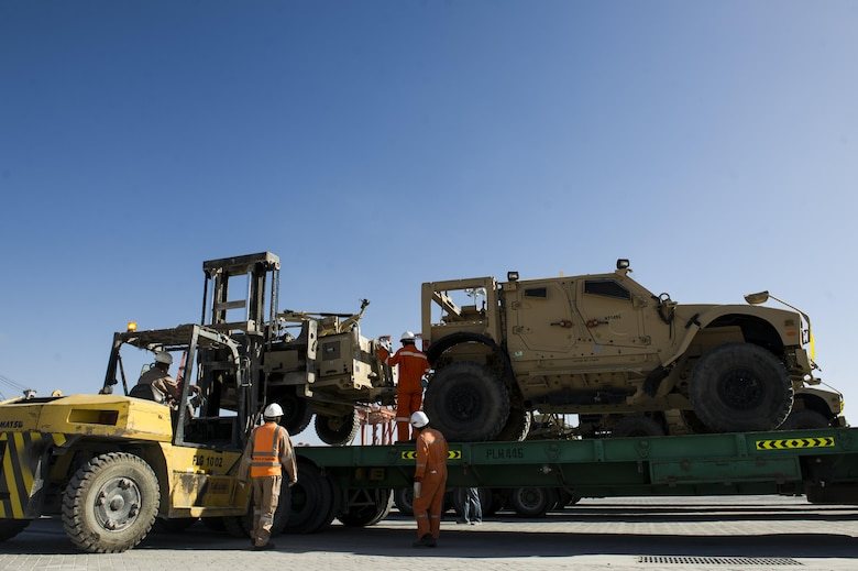 Contractors with the 405th Air Expeditionary Group unload a Mine Resistant Ambush-Protected vehicle from a flatbed trailer at the sea port at an undisclosed location in Southwest Asia, Dec. 31, 2013. The 405th AEG supports U.S. Central Command's Deployment and Distribution Operation Center, a strategically located air, land and sea logistics hub, playing a critical role in the U.S. departure from Afghanistan. (U.S. Air Force photo by Staff Sgt. Stephany Richards)