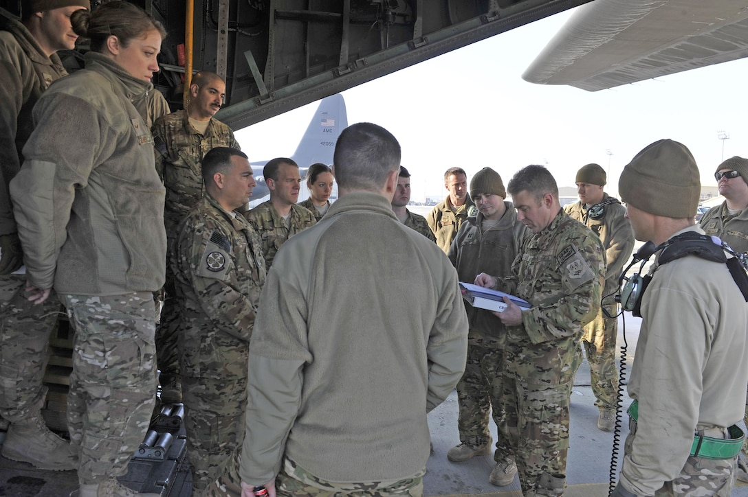Maj. Kurt Wampole briefs his crew and passengers Jan. 9, 2013, before his flight out of Bagram Airfield, Afghanistan. Wampole was on the first of the C-130H Hercules model aircraft to permanently relocate out of Bagram to make room for the newer C-130J model aircraft. Wampole is a C-130 pilot. (U.S. Air Force photo/Senior Master Sgt. Gary J. Rihn)