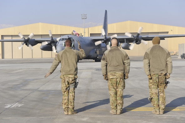 Tech. Sgt. Keith LaFontaine, accompanied by Senior Airman Larry Webster and Tech. Sgt. Richard Mulhollen, marshals out a C-130H Hercules Jan. 9, 2013, before its flight out of Bagram Airfield, Afghanistan. The aircraft was the first of the C-130H model aircraft to permanently relocate out of Bagram to make room for the newer C-130J model aircraft. (U.S. Air Force photo/Senior Master Sgt. Gary J. Rihn)