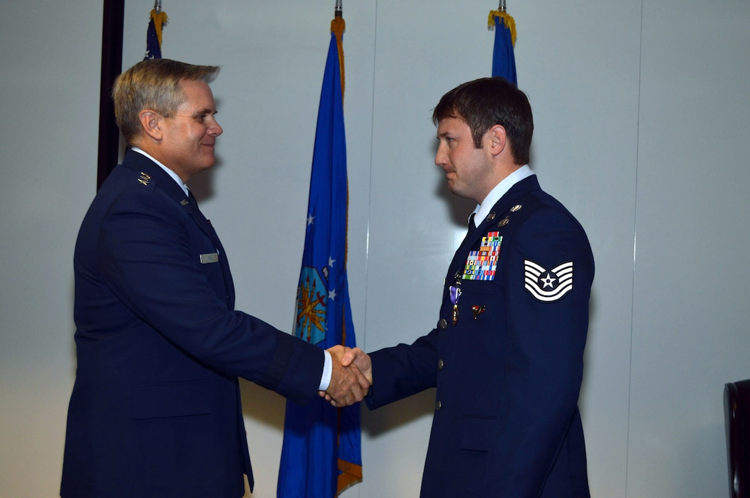 Lt. Gen. Eric Fiel, Air Force Special Operations Command commander, awards the Purple Heart medal to Tech. Sgt. Jeremy Whiddon, 21st Special Tactics Squadron, Jan. 10, 2014, at Pope Army Airfield, Fort Bragg, N.C., for wounds received in action on May 29, 2013. (U.S. Air Force photo by Marvin Krause)