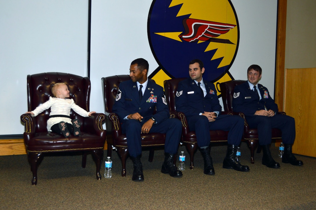 Master Sgt. Delorean Sheridan smiles at his daughter Kinsley, while Staff Sgt. Christopher Baradat and Tech. Sgt. Jeremy Whiddon look on during a 21st Special Tactics Squadron awards ceremony, presided by Lt. Gen. Eric Fiel, Air Force Special Operations Command commander, who awarded Silver Star medals to Sheridan and Baradat and a Purple Heart medal to Whiddon, Jan. 10, 2014, at Pope Army Airfield, Fort Bragg, N.C. (U.S. Air Force photo by Marvin Krause)