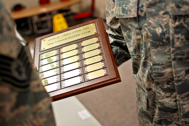"""U.S. Air Force Tech. Sgt. Alex R. Sea, vehicle equipment maintenance specialist with the 182nd Logistics Readiness Squadron, right, displays the plaque of winners after the sixth-annual chili cook off at the 182nd Airlift Wing, Peoria, Ill., Jan. 8, 2014. The competition placed 13 contestants and their homemade chili recipes against each other to compete for best look and smell, best consistency, and best taste. Sea won in both the best consistency and most overall points categories for his Jabbo Chili recipe. He was awarded a five-year membership to the wing's consolidated club and had his name added to the winners' plaque. The event brought out approximately 120 unit members to sample the various white and traditional red entries, and raised $490 in support of operating the wing's consolidated club. Sea enjoys the yearly event because he gets to have good chili with good people, he said. """"It's a good way to get out and mingle and talk to the people you don't usually see on a day-to-day basis."""" (U.S. Air National Guard photo by Staff Sgt. Lealan Buehrer/Released)"""