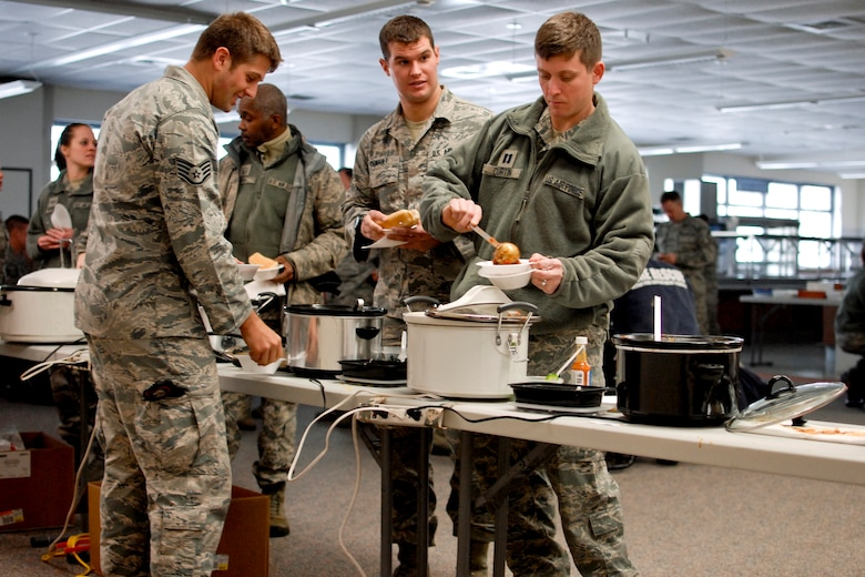 """Airmen of the 182nd Airlift Wing sample chili during the sixth-annual chili cook off at the 182nd Airlift Wing, Peoria, Ill., Jan. 8, 2014. The competition placed 13 contestants and their homemade chili recipes against each other to compete for best look and smell, best consistency, and best taste. The event brought out approximately 120 unit members to sample the various white and traditional red entries, and raised $490 in support of operating the wing's consolidated club. U.S. Air Force Tech. Sgt. Alex R. Sea, vehicle equipment maintenance specialist and winner of the 2014 competition, enjoys the yearly event because he gets to have good chili with good people, he said. """"It's a good way to get out and mingle and talk to the people you don't usually see on a day-to-day basis."""" (U.S. Air National Guard photo by Staff Sgt. Lealan Buehrer/Released. Image was cropped to emphasize the subjects.)"""