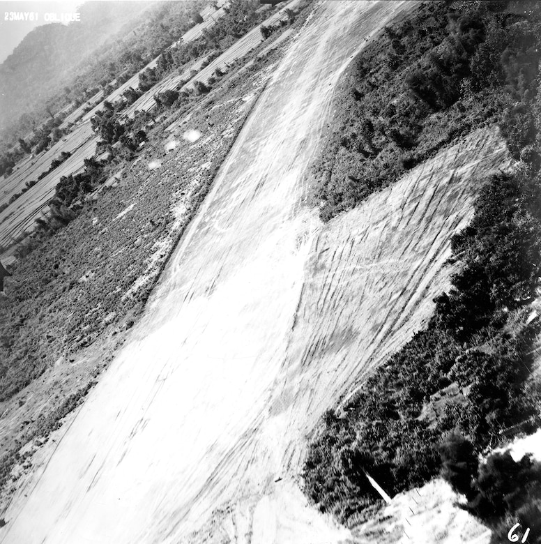 Reconnaissance image of Vang Vieng airfield, Laos, from a PROJECT FIELD GOAL flight in May 1961. At the time, the Soviets were using this airstrip to resupply Pathet Lao insurgents. Visible in the photo is smoke from three anti-aircraft guns firing at the RT-33A. (U.S. Air Force photo)