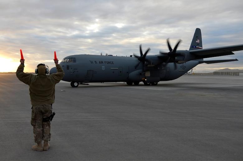 A U.S. Air Force Airman taxis the final C-130J Super Hercules at Kandahar Airfield, Afghanistan, Jan. 12, 2013. The C-130J Super Hercules will take over for the C-130 Hercules at Bagram Airfield, after four months at Kandahar. (U.S. Air Force photo by Senior Airman Kayla Newman/Released)