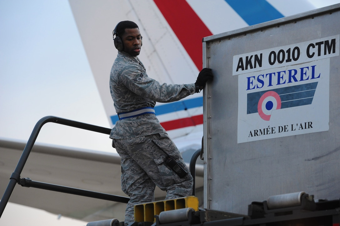 Airman 1st Class Christen Andrews, 728th Air Mobility Squadron aircraft services, monitors the downloading of cargo boxes onto a 60k loader Jan. 9, 2014, at Incirlik Air Base, Turkey. The cargo arrived along with more than 100 German soldiers who will continue to Kahramanmaras, Turkey to replace the German personnel who have been deployed there to man two Patriot missile batteries in support of NATO's commitment to enhance Turkish air defenses against Syrian aggression. The 728th AMS and 39th Air Base Wing continue to provide a variety of support to U.S., Dutch and German NATO personnel through aircraft and personnel processing, transportation, lodging and morale and welfare services. (U.S. Air Force photo illustration by 1st Lt. David Liapis/Released)