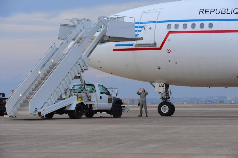 Airman 1st Class William Kooyman, 728th Air Mobility Squadron passenger services technician, marshals a staircase truck up to a French air force Airbus A310 that landed at Incirlik Air Base, Turkey with a troop of German soldiers Jan. 9, 2014. The 728th AMS has been providing support to the NATO Patriots to Turkey mission for more than a year. The soldiers aboard this aircraft will travel to Kahramanmaras, Turkey where they will replace deployed German soldiers currently manning two Patriot missile batteries set up to increase Turkey's air defense capabilities against Syrian ballistic missile threats. (U.S. Air Force photo by 1st Lt. David Liapis/Released)
