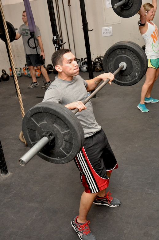 "Air Force Senior Airman Carlos Amaya, 380th Expeditionary Security Forces Squadron, lifts the bar as part of a ""clean"" during a CrossFit class at the tactical fitness facility at an undisclosed location in Southwest Asia, Jan. 3, 2014. (U.S. Air Force photo by Maj. Khalid Cannon/Released)"