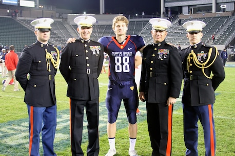 CARSON, CA— Tyler Newsome, a punter and kicker for the Semper Fidelis All-American Bowl East team, poses with Marines at the conclusion of the Semper Fidelis All-American Bowl at The StubHub Center in Carson, Calif., Jan. 5. Newsome, a native of Carrollton, GA, is committed to the University of Notre Dame. The Semper Fidelis All-American Bowl is unique because the players are among the most talented players in the nation and are high-academic performers and leaders in their communities. The Semper Fidelis All-American Bowl works to build effective leaders and quality citizens by instilling Marine Corps values. The Semper Fidelis All-American Bowl brings selected players together with U.S. Marines and football coaches to develop skills not only important to football, but throughout life, such as leadership, self-confidence and teamwork. (U.S. Marines Corps photo by Cpl. Courtney G. White/released)