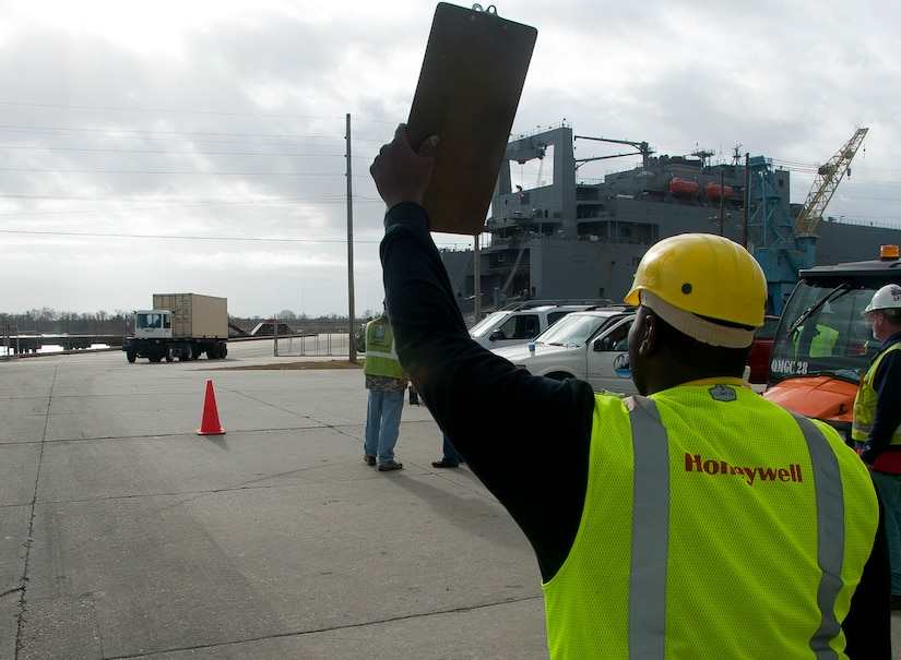 Tyrone Aken, Honeywell material coordinator, directs a truck into the shipyard after it rolls off the USNS Pomeroy (T-AKR-316), Jan. 7, 2014 at Joint Base Charleston – Weapons Station, S.C. Once equipment is in the shipyard, the material coordination team scan the items before it is turned over to the Army Strategic Logistics Activity Charleston for maintenance. Once re- loaded onto a ship, the equipment is prepositioned overseas for 18 to 36 months near potential hotspots until it is needed by the warfighter. (U.S. Air Force photo/Staff Sgt. William O'Brien)