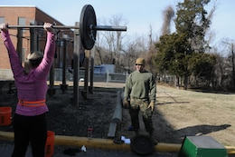 CrossFit Quantico coach Capt. Adam Tabalno advises Shanna Bonaudi, whose husband is attending the Expeditionary Warfare School, on proper push press form during the Jan. 8, 2014, workout.