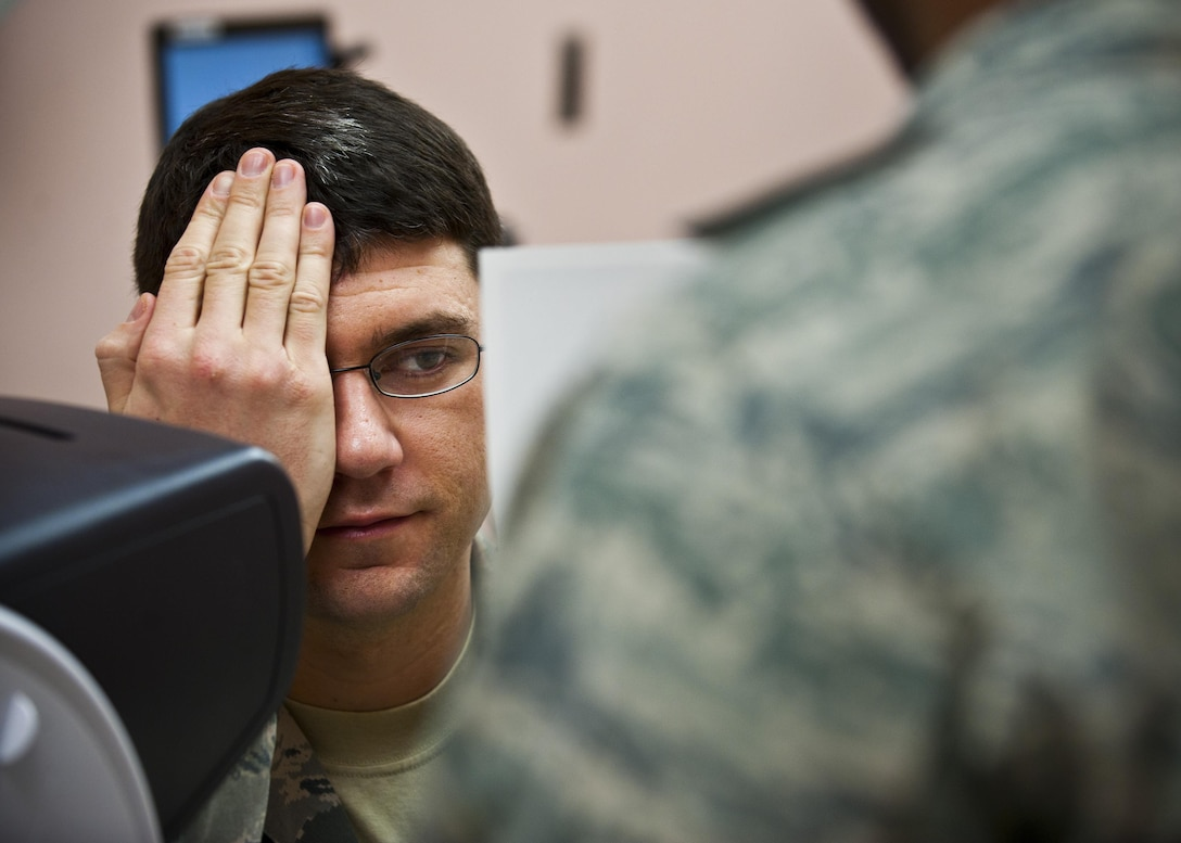 Staff Sgt. Shane Lahaie receives an eye exam during an occupational health exam Jan. 10, 2014, at Nellis Air Force Base, Nev. An eye exam assesses vision and ability to focus on and discern objects. Lahaie is a 820th REDHORSE power production journeyman. (U.S. Air Force photo/Senior Airman Brett Clashman)
