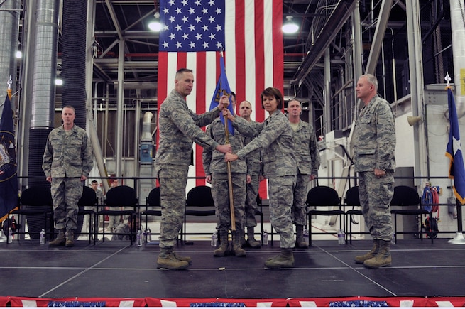Col. Darwin L. Craig presents Lt. Col. Susan L. Melton with the unit flag during the 151st Maintenance Group Change of Command.  Col. David P. Osborne relinquished command to Lt. Col. Melton at the January 11, 2014 ceremony held at the Utah Air National Guard Base. (Utah National Guard Photo by SSgt Annie Edwards/released)