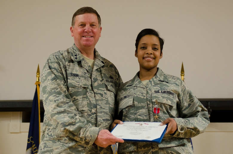 Kentucky's adjutant general, Maj. Gen. Edward W. Tonini, presents Master Sgt. Zakiya Taylor with the Bronze Star Medal during an award ceremony held Jan. 12, 2014 at the Kentucky Air National Guard Base in Louisville, Ky. Taylor earned the award for exceptionally meritorious achievement while serving in Afghanistan as part of Kentucky Agribusiness Development Team V, a multi-disciplinary task force charged with helping the nation develop a sustainable farming economy. (U.S. Air National Guard photo by Airman 1st Class Joshua Horton)