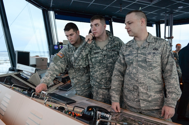 U.S. Army Spcs. Paul Murray and Christopher Smades, Fox Company 1-51, Aviation Battalion air traffic control specialists, practice standard control tower measures with Master Sgt. Dustin Rogstad, 354th Operations Support Squadron tower control chief, Jan. 14, 2014, Eielson Air Force Base, Alaska. Murray and Smades have been training since August with Air Force controllers on fixed-wing air traffic control procedures. (U.S. Air Force photo by Airman 1st Class Peter Reft/Released)