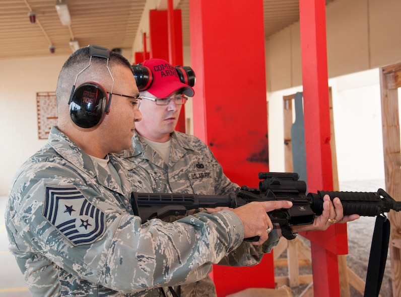 Chief Master Sgt. Gerardo Tapia, Air Education and Training Command command chief, checks a rifle before loading it and prepares to shoot a rifle at the Combat Arms Training and Marksmanship range on Laughlin Air Force Base, Texas, Jan. 9, 2014. After firing the rifle he helped present the AETC Outstanding Security Forces Flight Level NCO of the Year Award to Staff Sgt. Tynesha Sweeney, 47th Security Forces Squadron report analysis technician. (U.S. Air Force photo/Airman 1st Class Jimmie D. Pike)