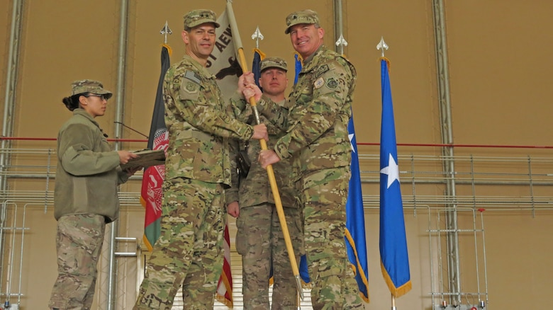 U.S. Air Force Maj. Gen. Kenneth Wilsbach, Commander, 9th Air and Space Expeditionary Task Force-Afghanistan; Deputy Commander-Air, U.S. Force-Afghanistan; and Deputy Chief of Staff-Air, International Security Assistance Force Joint Command, receives the 451st Air Expeditionary Wing guidon from Brig. Gen. Michael Frantini, 451st AEW commander and Commander, Kandahar Airfield, in a transition ceremony at Kandahar Airfield, Afghanistan, Jan. 13, 2014. The 451st Air Expeditionary Wing was transitioned to an Air Expeditionary Group due to a change in mission.(U.S. Air Force photo by Senior Airman Alexandria Bandin/Released)