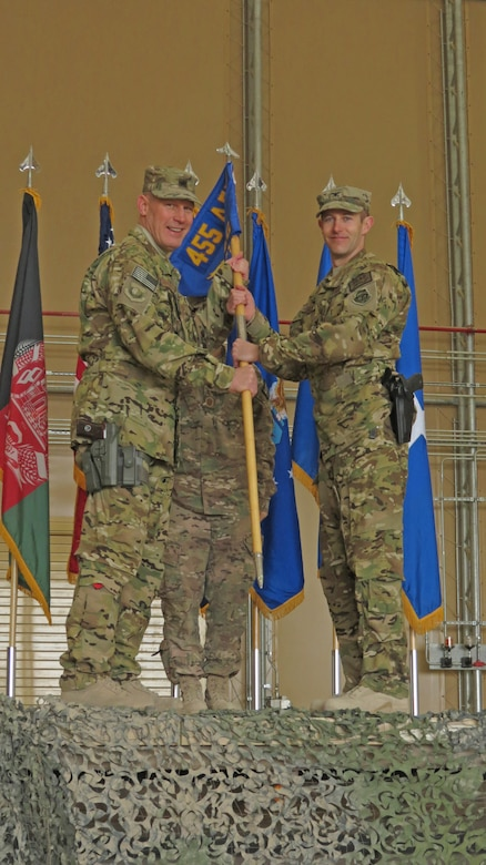 U.S. Air Force Col. Scott Campbell, 451st Air Expeditionary Group commander, receives the new 451st AEG guidon from Brig. Gen. Patrick Malackowski, 455th Air Expeditionary Wing commander, in a transition ceremony at Kandahar Airfield, Afghanistan, Jan. 13, 2014. The 451st Air Expeditionary Wing was transitioned to an AEG due to a change in mission.(U.S. Air Force photo by Senior Airman Alexandria Bandin/Released)