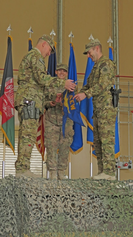 U.S. Air Force Brig. Gen. Patrick Malackowski, 455th Air Expeditionary Wing commander and Col. Scott Campbell, 451st Air Expeditionary Group commander, unfurl the new 451st AEG guidon in a transition ceremony at Kandahar Airfield, Afghanistan, Jan. 13, 2014. The 451st Air Expeditionary Wing was transitioned to an AEG due to a change in mission.(U.S. Air Force photo by Senior Airman Alexandria Bandin/Released)