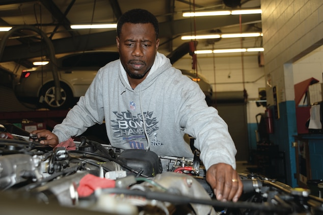 Lucien Sejour, equipment specialist, Marine Corps Systems Command, replaces the engine on a 1997 Toyota Camry he is repairing for his son.