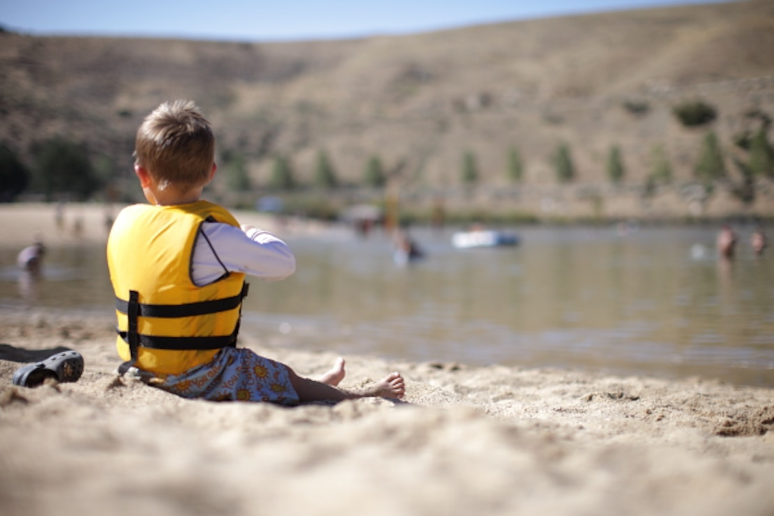 A young man enjoy the buzz around the beach on a hot summer day.  Playing safe around natural waters rests in large part upon lifejackets and close supervision.