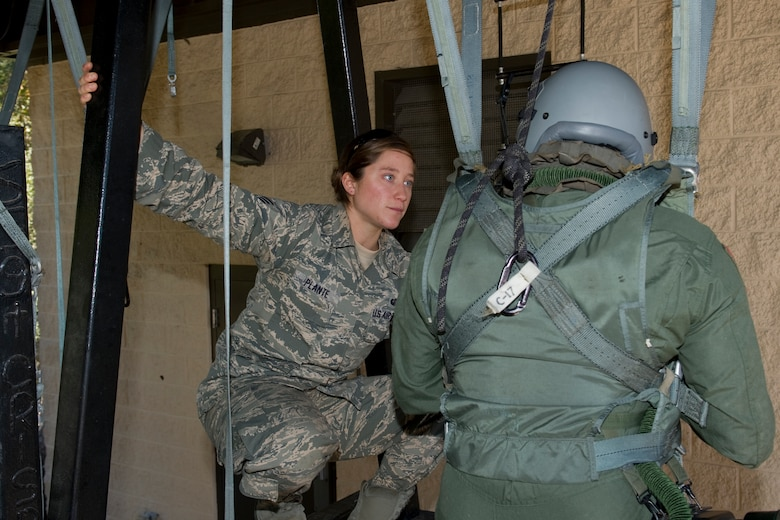 Senior Airman Charlene Plante, 1st Special Operations Support Squadron survival, evasion, resistance and escape instructor, advises an aircrew member on the proper way to escape a parachute during a SERE refresher course at Hurlburt Field, Fla., Jan. 14, 2014. Plante is one of about a dozen females who have successfully completed the SERE instructor course. (U.S. Air Force photo/Senior Airman Naomi Griego)