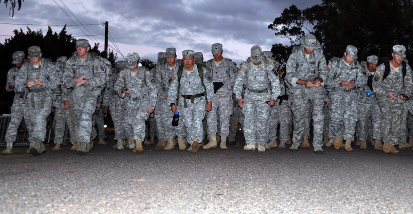 Members of Joint Task Force-Bravo take the first step of a road march as part of German Armed Forces Proficiency Badge Qualification at Soto Cano Air Base, Honduras, Jan. 16, 2014.  Several members of Joint Task Force-Bravo are attempting to qualify for the badge this week. In order to qualify for the badge, service members must pass both a fitness test and a military training test, administered by a German Sergeant Major. This morning, Task Force members completed a road march of distances ranging from 6 to 12 kilometers while wearing a 35-pound ruck sack. (U.S. Air Force photo by Capt. Zach Anderson)