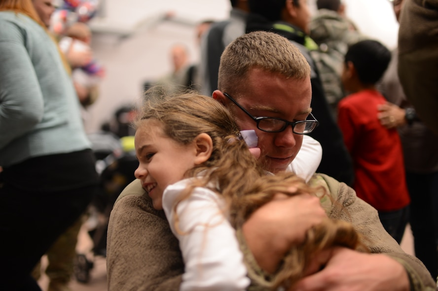 SPANGDAHLEM AIR BASE, Germany – U.S. Air Force Senior Airman Shayne Kusserow hugs his daughter, Nevaeh, after returning from a deployment with the 606th Air Control Squadron Jan. 15, 2014. The 606th ACS is one of the 52nd Operations Group's three squadrons which comprise the flying component of the 52nd Fighter Wing. (U.S. Air Force photo by Senior Airman Gustavo Castillo/Released)