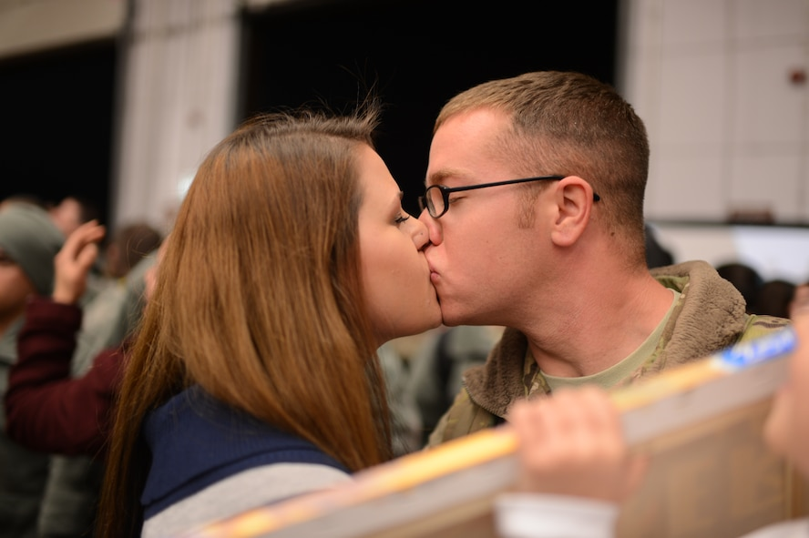 """SPANGDAHLEM AIR BASE, Germany – U.S. Air Force Senior Airman Shayne Kusserow, 606th Air Control Squadron, kisses his wife, Emma, after a six-month deployment to Southwest Asia Jan. 15, 2014. 606th ACS Airmen constantly """"train as they fight"""" during annual week-long field exercises, in which they exercise their ability to transport equipment and set up a control and reporting center. (U.S. Air Force photo by Senior Airman Gustavo Castillo/Released)"""