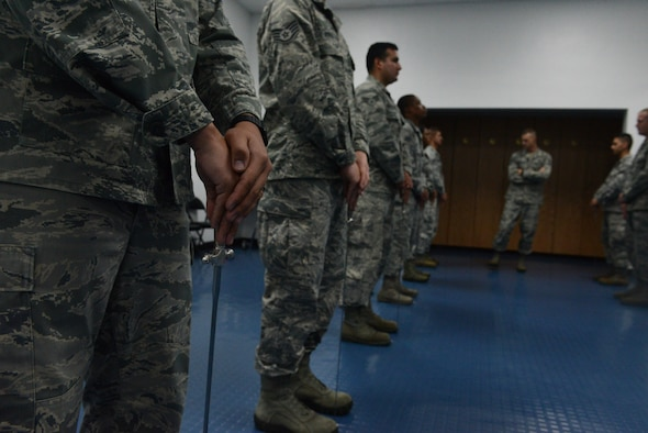 Tech. Sgt. Anthony Miller, Blue Knight Honor Guard lead trainer (center back), inspects the Andersen Blue Knights Honor Guard team as they stand at the position of ceremonial at ease Jan. 8, 2014, on Andersen Air Force Base, Guam. The honor guard's mission is to maintain and employ a ceremonial capability to represent the Air Force at public and official ceremonies. (U.S. Air Force photo by Airman 1st Class Emily A. Bradley/Released)