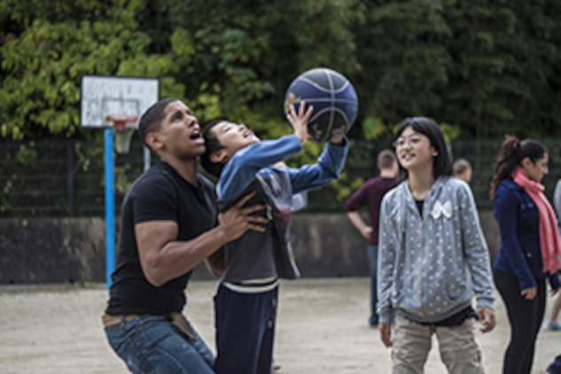 Lance Cpl. Emmanuel Torres, an aircraft electronic countermeasures system technician with Marine Aviation Logistics Squadron 12, helps a child from a Yamaguchi city children's home throw a basketball during a Single Marine Program trip, Oct. 19, 2013. Oana Ivanoff, SMP Marine lounge manager, said she plans on returning to the Yamaguchi city children's home in December.