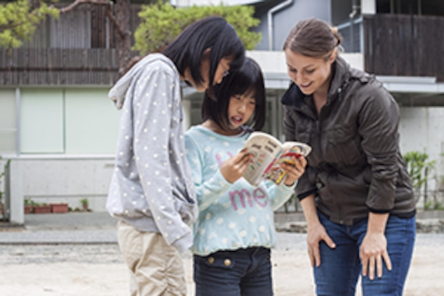 Lance Cpl. Dianna Ganzhorn, an embarkation specialist with Combat Logistics Company 36, reads with children from a Yamaguchi city children's home during a Single Marine Program trip, Oct. 19, 2013. Ganzhorn said that she also brought a notebook and pencil in the hopes of better communicating with the children.