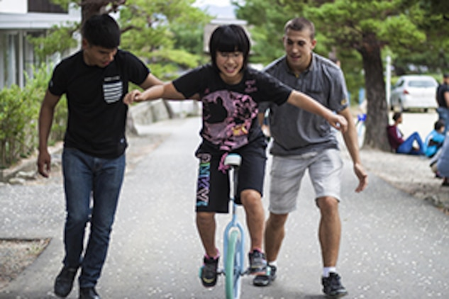 Lance Cpl. Carlos Santos, left, an aviation technician with Marine Attack Squadron 214, and Lance Cpl. Mitchell Jameson, an S-2/S-6 clerk with Combat Logistics Company 36, assist a child from a Yamaguchi city children's home in riding a unicycle during a Single Marine Program trip, Oct. 19, 2013. The SMP provides several opportunities throughout the year for service members to give back to the local community.