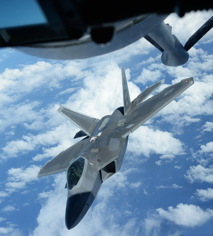 An F-22 Raptor from the 199th Fighter Squadron positions itself to receive fuel from a KC-135 Stratotanker from the 96th Air Refueling Squadron Jan. 10, 2014, near Joint Base Pearl Harbor-Hickam, Hawaii. Both aircraft and their crews participated in the Inaugural Total Force Integration Warrior Day, a training event that tested the cooperation and capabilities of multiple base agencies. The training highlighted the importance of integrating operations of active-duty, Hawaii National Guard and Air Force Reserve units. (U.S. Air Force photo/Staff Sgt. Alexander Martinez)