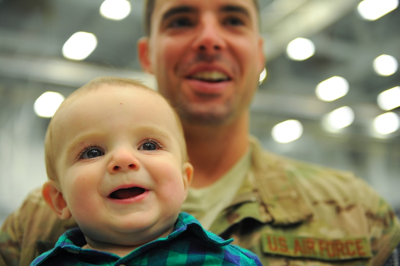 Aiden Robillard smiles in the arms of his father, Staff Sgt. Tim Robillard, Jan. 12, 2014, at Hurlburt Field, Fla. Robillard was met by his wife and son after returning home from deployment. Robillard is a 801st Special Operations Aircraft Maintenance Squadron electric and environmental systems maintainer. (U.S. Air Force photo/Staff Sgt. John Bainter)