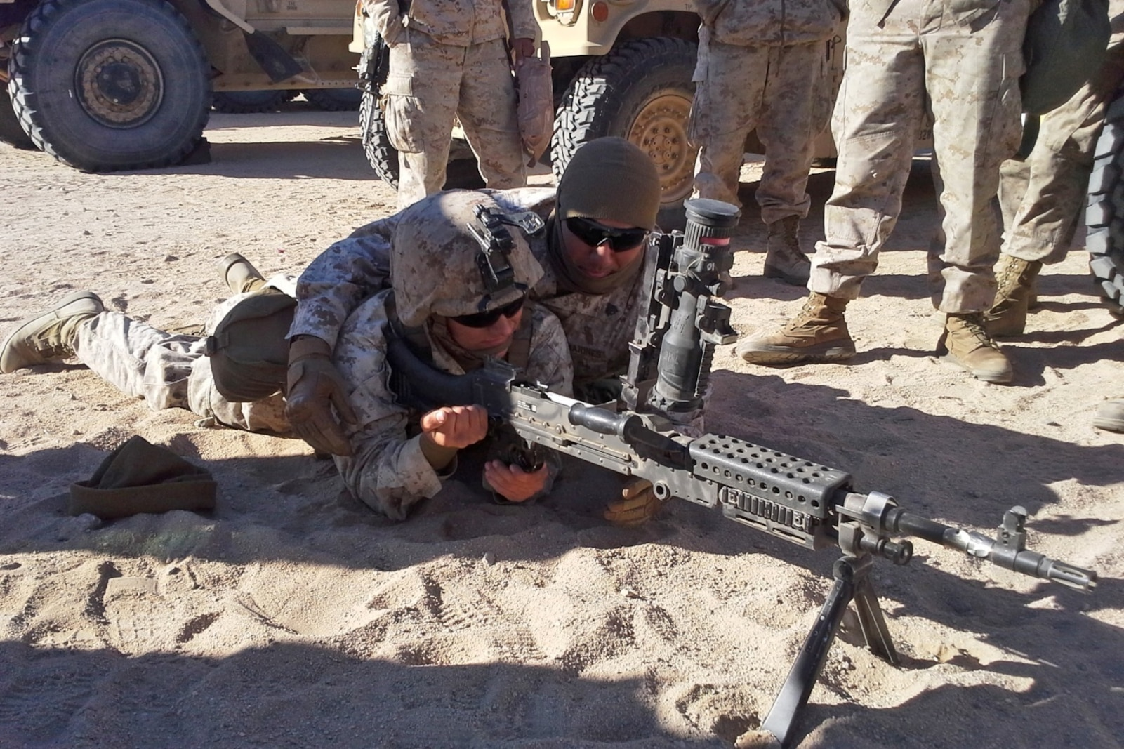 Lance Cpl. Dustin Luse, left, demonstrates how to operate the M240B with the help of Sgt. Joseph Lopez, right, both with Motor Transportation Company, Combat Logistics Battalion 5, Combat Logistics Regiment 1, 1st Marine Logistics Group, aboard Marine Air Ground Combat Center Twentynine Palms, Calif., Dec. 11, 2013. Luse, of Vidor, Texas, recently supported Exercise Steel Knight 2014. SK14 is an annual exercise designed to prepare the 1st Marine Division for deployment.