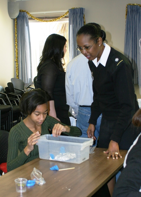 ALBUQUERQUE, N.M., -- District Commander Lt. Col. Antoinette Gant watches a student build a model dam, Jan. 3, 2014. Thirty students gathered at the District's main office to explore STEM-related career fields.