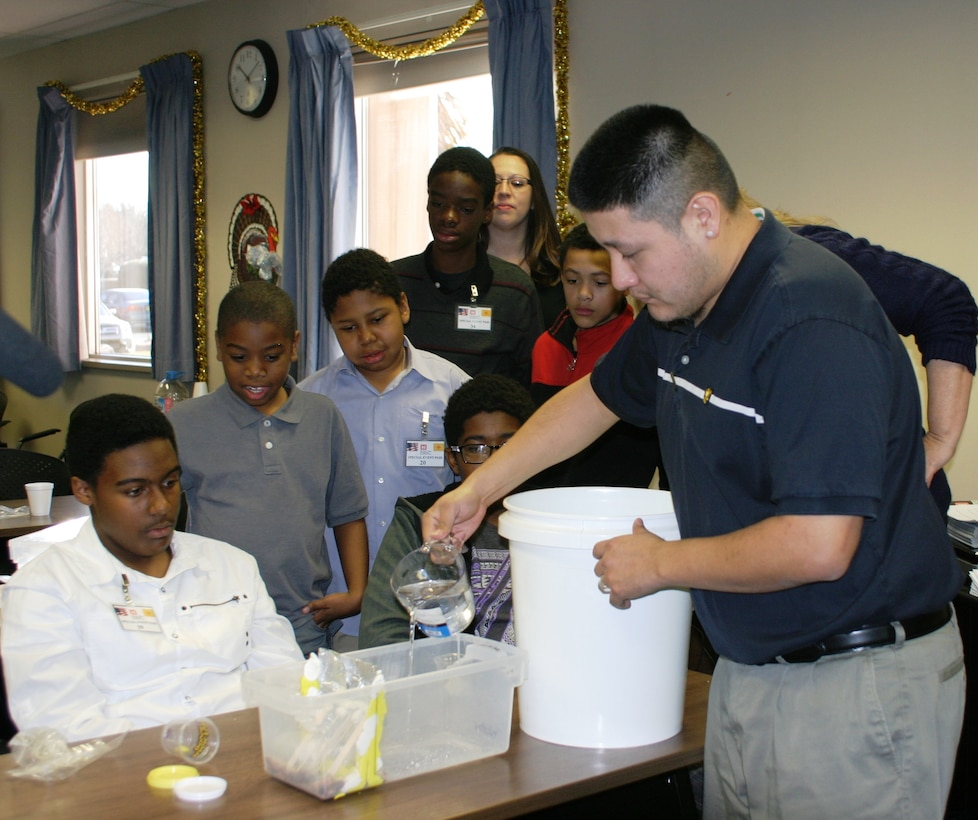 ALBUQUERQUE, N.M., -- Architect Lionel Romero pours water on a model dam to test its design Jan. 3, 2014. Students gathered at the District's main office to learn more about STEM and the Corps of Engineers.