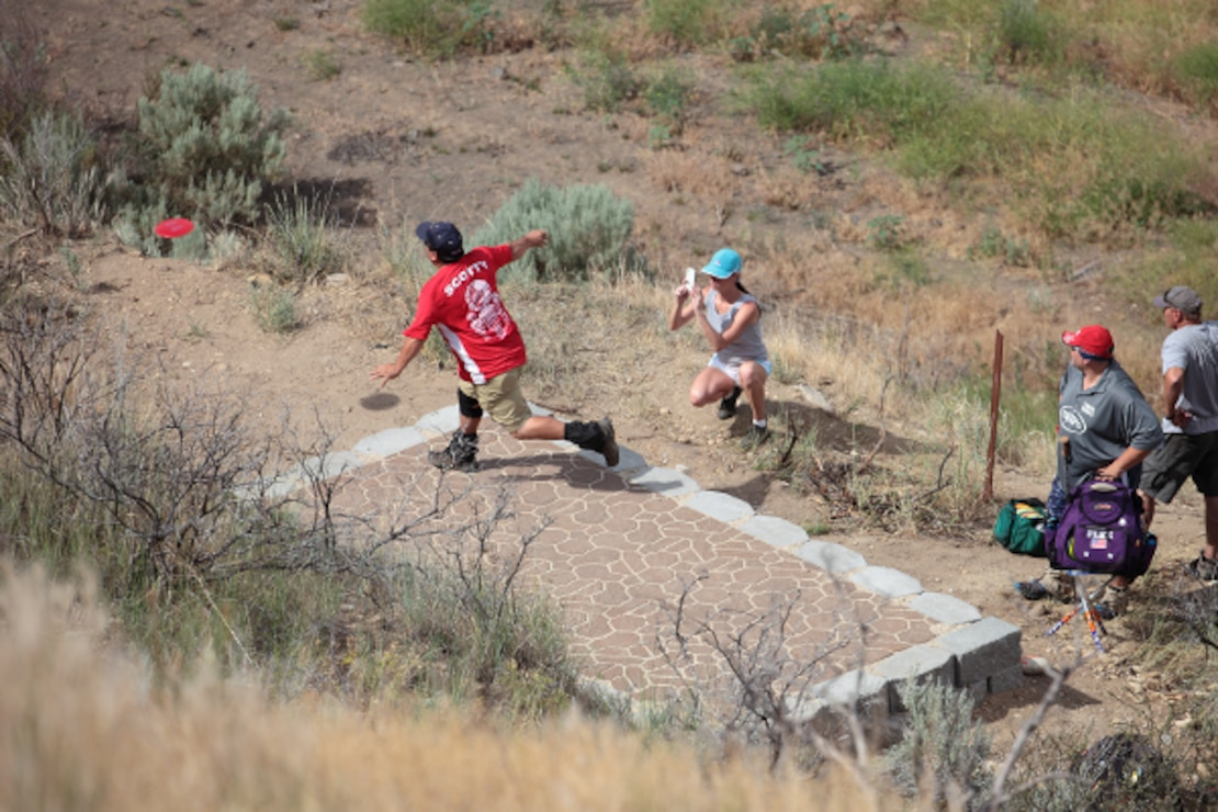 A group of disc golfers take their turns attempting an Ace on tee 7 of the Gold Course at Lydle Gulch in Lucky Peak Dam Recreation Area.