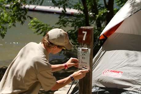 A volunteer posts a recreation.gov camping reservation at Macks Creek Park.