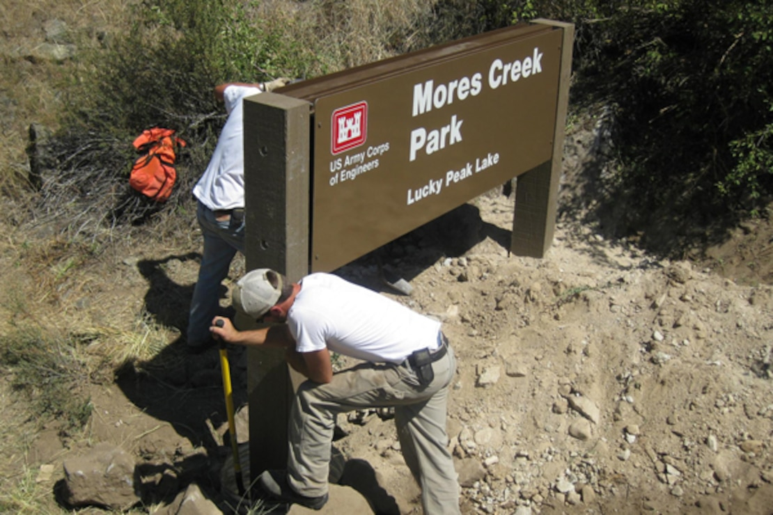 Lucky Peak Lake employees install an identification sign for Mores Creek Park.