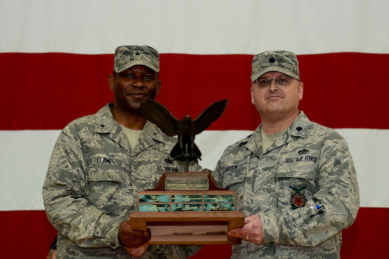 U.S. Air Force Brig. Gen. Calvin Elam, Assistant Adjutant General for Air for the South Carolina Air National Guard, presents Lt. Col. Timothy Dotson, the 169th Civil Engineer Squadron commander, with the trophy for being named the 2013 Unit of the Year, during a mass formation in the main hangar, Jan. 12, 2014.  (U.S. Air National Guard photo by Tech. Sgt. Caycee Watson/Release)