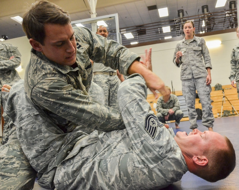 Capt. Brian Dicks, 55th Rescue Squadron, attempts a submission on Tech Sgt. Joshua Holliday, 612th Air and Space Operations Center, during the Modern Army Combatives Program (MACP) Basic Combatives Course Level 1 at Davis-Monthan Air Force Base, Ariz., Jan. 16, 2014. The 40-hour course focuses on the three phases of basic fighting strategy; close the distance, gain the dominate position, and how to finish the fight. (U.S. Air Force photo by Staff Sgt. Adam Grant/Released)